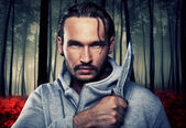 Man with a knife in a dark forest — Stock Photo