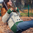 Autumn portrait of a young woman on a swing — ストック写真
