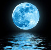 Full blue moon over water with reflections — Stock Photo