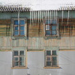 Stock Photo: Icicles on roof of old wooden house.