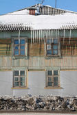 Icicles on the roof of an old wooden house. — Stock Photo