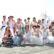 Постер, плакат: A lot of girls dressed as a bride on the march BOOM brides