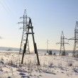Old wooden pole on the background of modern metal supports electrical lines. — Stock Photo #9419292