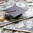 Stock Photo: Graduation cap on cash