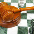 Legal gavel on a chess board with game pieces — Stock Photo