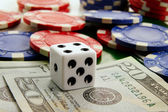 Stacked poker chips and dice with cash — Stock Photo