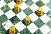 Euro coins arranged on a chess board as pieces — Stock Photo
