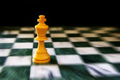 King on a chess board, against black background — Stock Photo