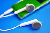 Closeup of ear phones and mp3 music player — Stock Photo
