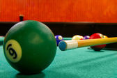 Pool table and balls shot from low angle, near ball is sharp — Stock Photo