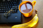 Cup of morning coffee with laptop and a banana — Stock Photo