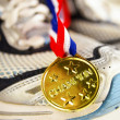 Stok fotoğraf: Gold medal and running shoes, closeup