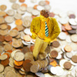 Business man figure standing in a pile of money — Stock Photo