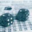 Two dice on a newspaper stock market page — Stock Photo #9337922