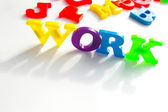 "Children's colorful plastic letters spelling ""work"" — Stockfoto"