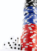 Stacked poker chips cash and dice on white — Stock Photo