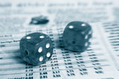 Two dice on a newspaper stock market page — Stock Photo