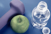 Bootle of water, weight and green apple — Stock Photo