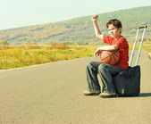 Little boy hitching on road — Stock Photo