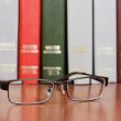 Stock Photo: Glasses on the bookshelf