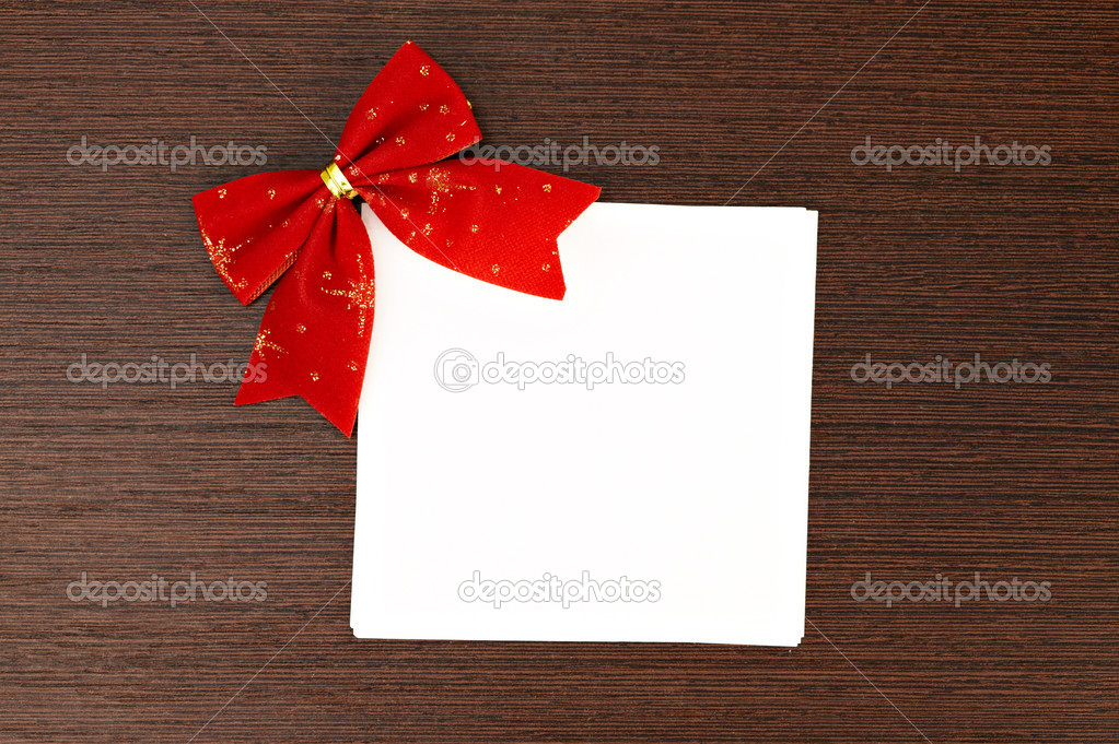 Paper gift note with a red christmas bow — Stock Photo #9164538