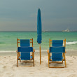 Stock Photo: Beach lounge chairs over cloudy sky