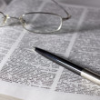 Stock Photo: Glasses with pen on book