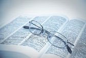 Closeup of opened book and glasses — Stock Photo