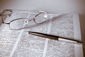 Open book with glasses and pen — Stock Photo