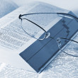 Closeup of opened books and glasses — Stock Photo