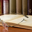 Glasses in front of an old books — Stock Photo