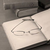 Open antique books with glasses — Photo
