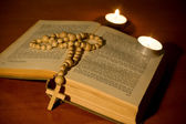 Cross over bible with candles — Stock Photo