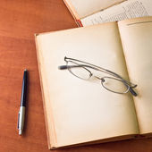 Old books with reading glasses and pen — Stock Photo