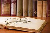 Vintage book and glasses in library — Stock Photo