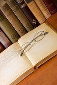 Old eyeglass on a old book — Stock Photo