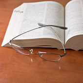 Closeup of opened book and glasses — ストック写真