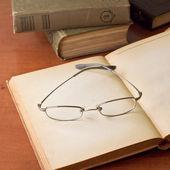 öppna antika böcker med glasögon — Stockfoto