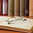 Book and glasses in library — Lizenzfreies Foto