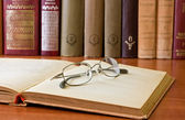 Boek en bril in bibliotheek — Stockfoto