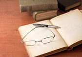 Opened book, pen and glasses — Stock Photo