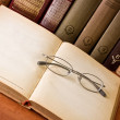 Stock Photo: Open antique book with glasses