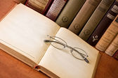 Open antique book with glasses — Stock Photo