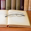 Glasses laying over an opened old book — Stock Photo