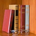 Retro books and glasses on bookshelf — Stock Photo #9331691