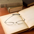 Pile of old books with reading glasses — Stock Photo