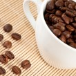 White cup of coffee and coffee beans — Stock Photo