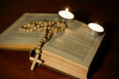 Wooden cross over bible with candles — Stock Photo
