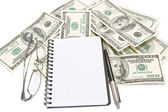 Pen, notepad and glasses on money background — Stockfoto