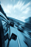 Car driving fast with blurry background — Stock Photo